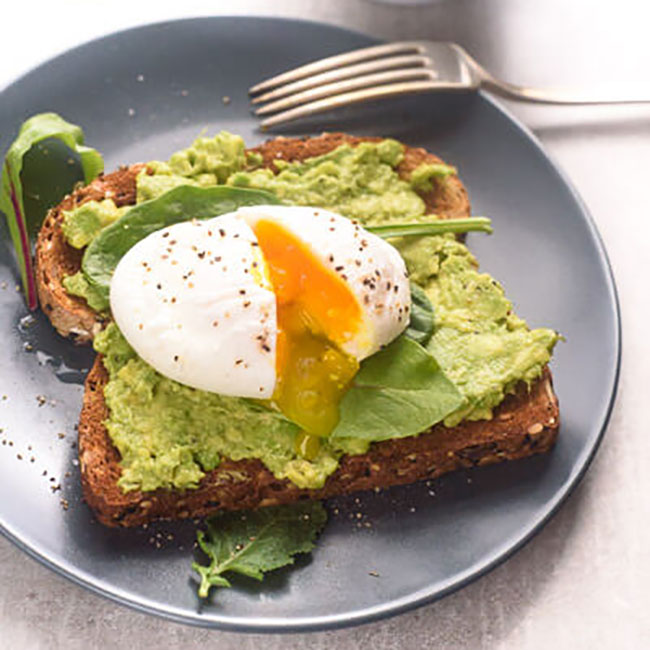 Avocado and poached egg on rye bread toast
